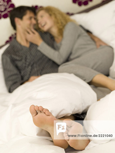 Young couple lying in bed  close-up of feet