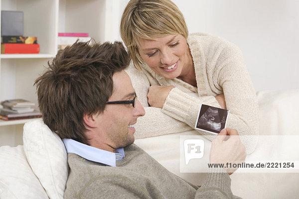Couple  Man looking at ultrasound photos
