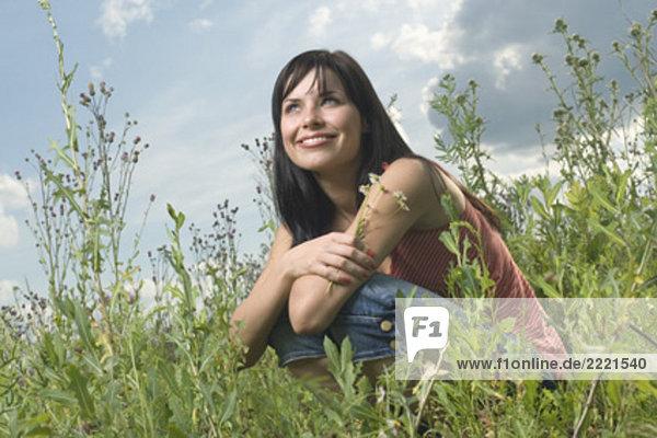 Portrait einer jungen Frau sitzen in hält Flowers Wiese Portrait einer jungen Frau sitzen in hält Flowers Wiese