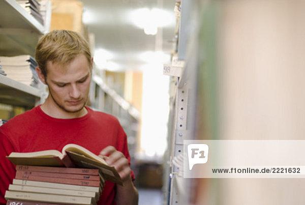 jungen männlichen Studenten Lesebuch in Schulbibliothek