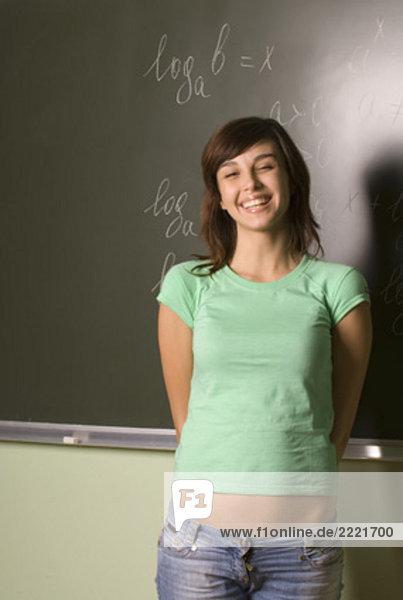 Porträt von lächelnd female Student standing in front of blackboard