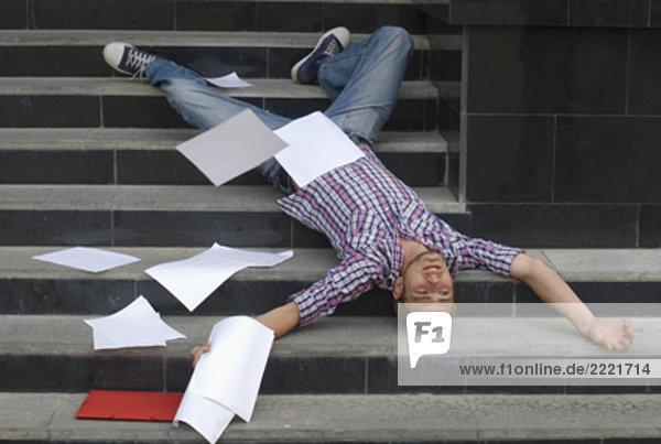 junger Student liegen auf dem Rücken auf Treppe umgeben von Schuldokumente