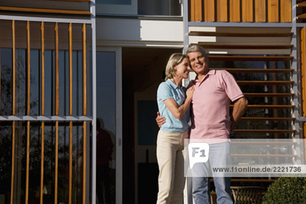 Portrait von reifes Paar standing in front of home