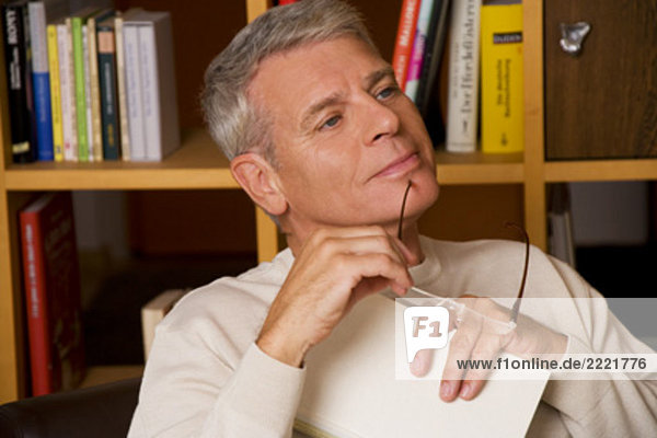 portrait of mature man holding spectacles und book