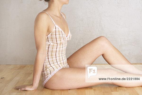 junge Frau sitzen auf Boden in ihre Unterwäsche