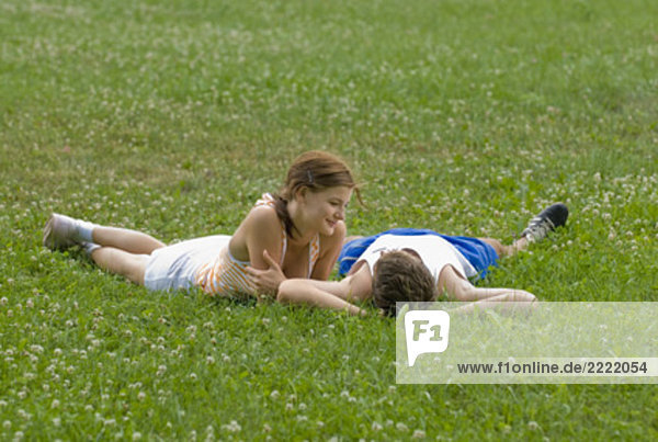 young couple lying on lawn in park flirting with each other