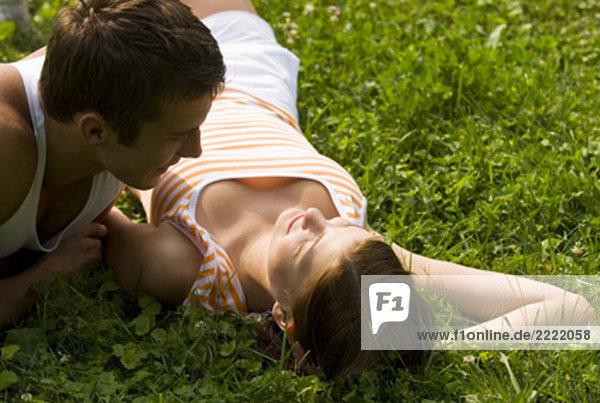 junges paar liegend auf Rasen im Park Flirten mit einander
