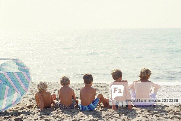 five boys - sitting on the beach