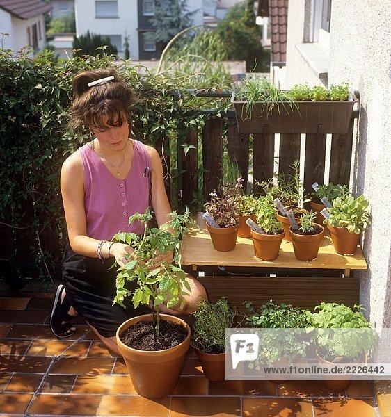 Frau auf Balkon mit verschiedenen Pflanzen