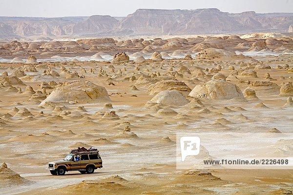 Geländewagen mit Felsformationen in der Wüste  weiß Wüste  Farafra  Ägypten Geländewagen mit Felsformationen in der Wüste, weiß Wüste, Farafra, Ägypten