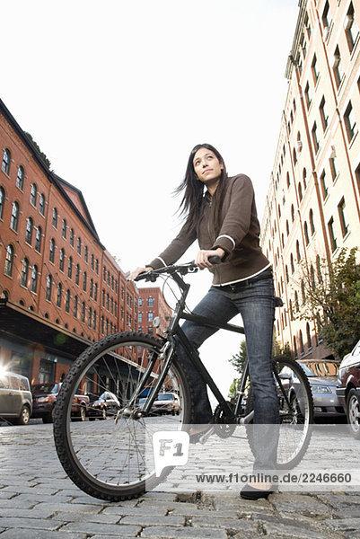 Hispanische Frau stehend mit Fahrrad