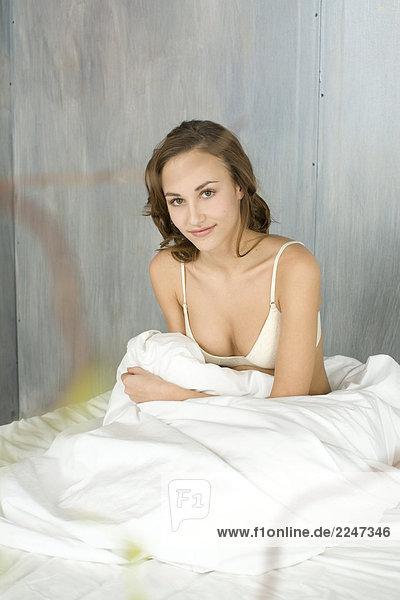 junge Frau sitzen auf dem Bett