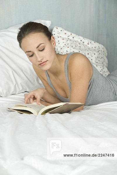 junge Frau Lesebuch im Bett