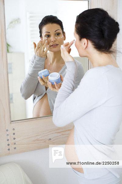 Schwangere Frau Apllying Gesichtscreme