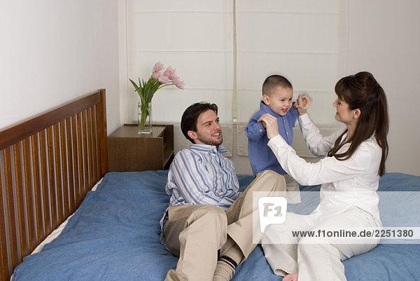 Familie zusammen sitzen auf dem Bett