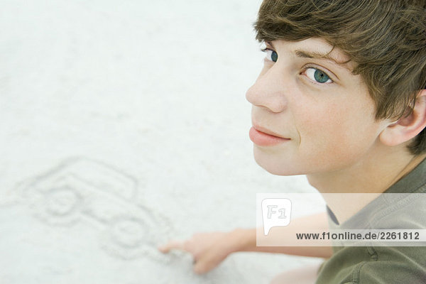 Teenage boy drawing car in sand  cropped view