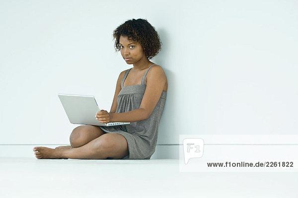 Junge Frau auf dem Boden sitzend  mit Laptop-Computer  lächelnd vor der Kamera