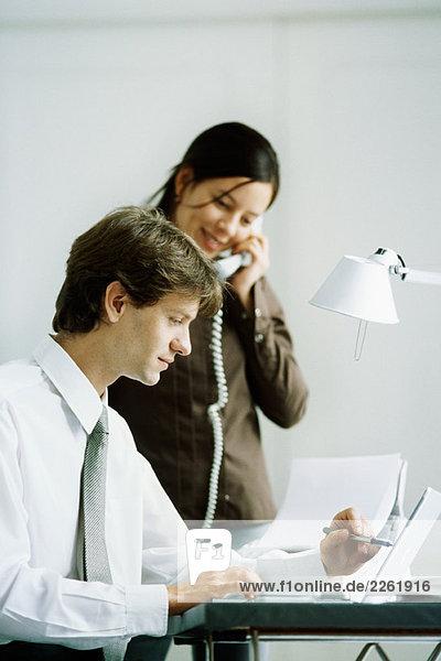 Männliche und weibliche Kollegen schauen gemeinsam auf den Laptop  Mann zeigt mit Stift  Frau hält Telefon