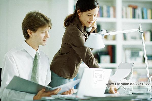Männliche und weibliche Kollegen am Schreibtisch  Mann mit Blick auf Laptop  Frau mit Telefon