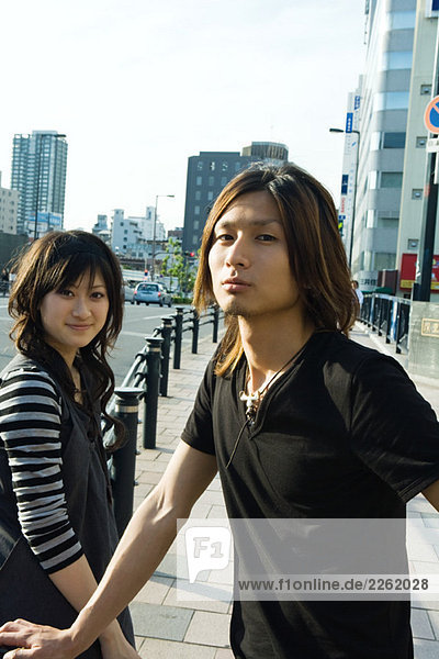 Junges Paar steht auf dem Bürgersteig  schaut in die Kamera  Frau lächelt