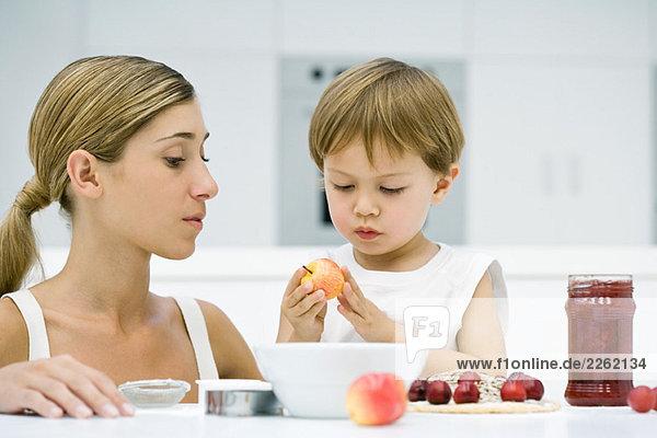 Mutter und Sohn kochen gemeinsam  Junge hält Apfel  beide schauen nach unten