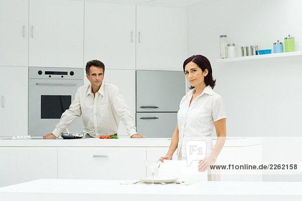 Paar in der Küche  Mann beim Kochen  Frau beim Tischdecken