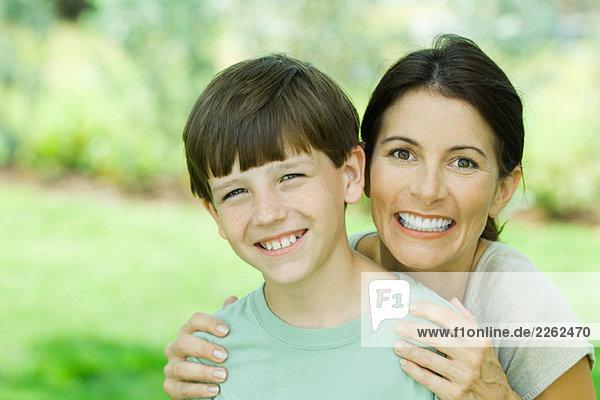 Mutter und Sohn lächeln gemeinsam vor der Kamera  Porträt