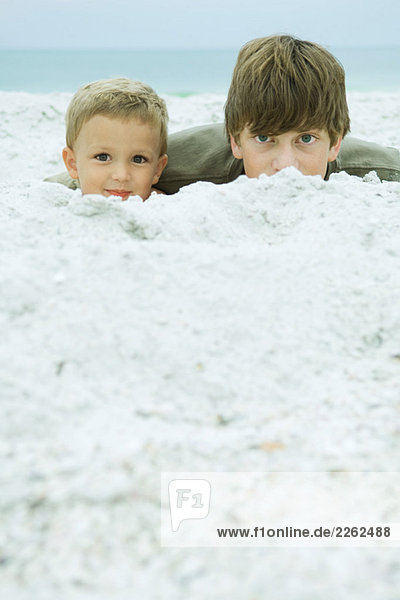 Two brothers at the beach  peeking over sand at camera