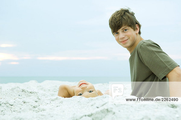 Two brothers at the beach  both smiling at camera