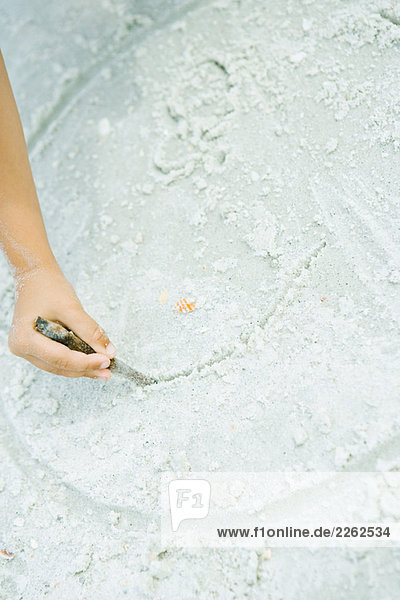 Child drawing in the sand with stick  cropped view of hand