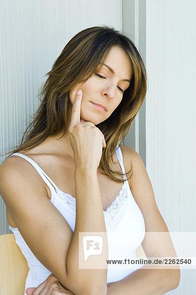 Frau berührt Gesicht  Hand unter dem Kinn  Blick nach unten