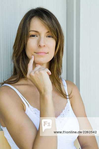 Woman touching face with forefinger  hand under chin  looking at camera