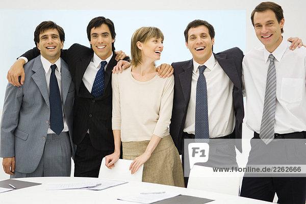 Team von Geschäftspartnern  die mit den Armen umeinander stehen  lächelnd  Gruppenbild