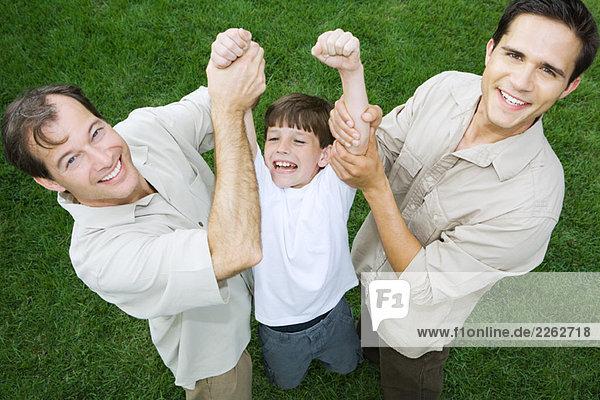 Zwei Männer  die den kleinen Jungen an den Armen halten  alle lächelnd  mit einem hohen Blickwinkel.