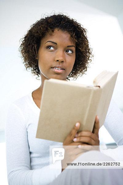 Junge Frau hält Buch  schaut weg  Nahaufnahme