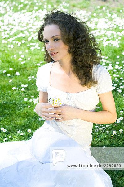 Junge Frau auf dem Boden saßen mit Blumen  Blick in die Kamera seitlich