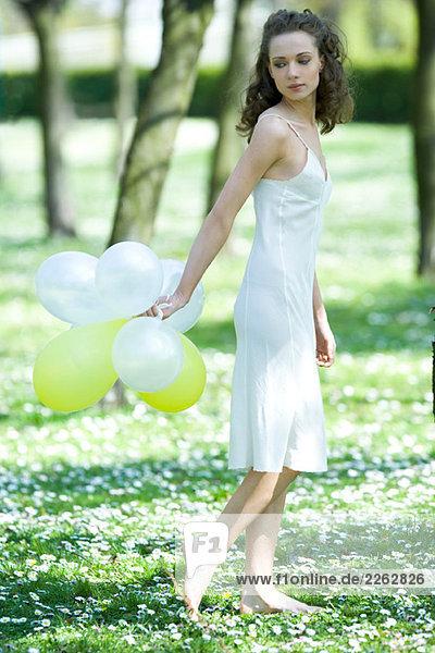 Junge Frau zu Fuß in Bereich der Blumen  halten Ballons hinter dem Rücken  übermäßigschulter