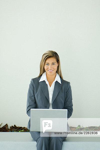 Geschäftsfrau sitzen  Laptop Computer verwendet  Lächeln in die Kamera