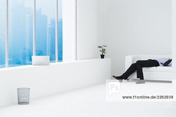 Kaufmann liegend auf Sofa in minimalistischen Hochhaus Wohnung  cropped Ansicht