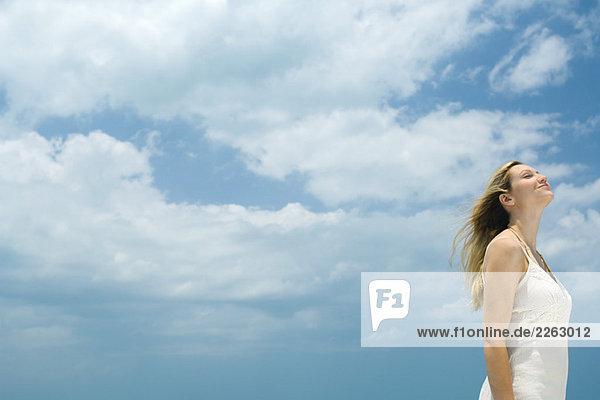 Junge Frau stehend im Freien mit Kopf zurück  Augen geschlossen  Side View  low angle