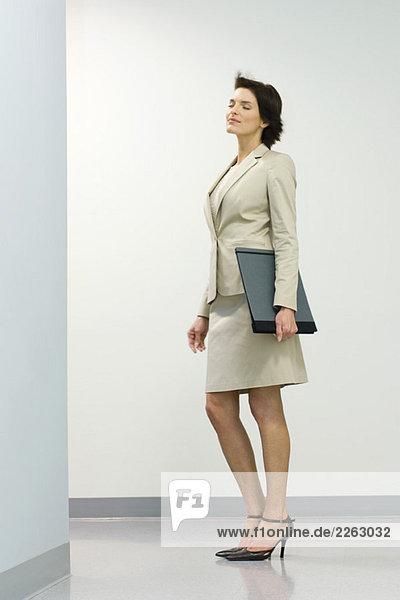 Geschäftsfrau im Flur mit Augen geschlossen  Haar zerzaust von breeze