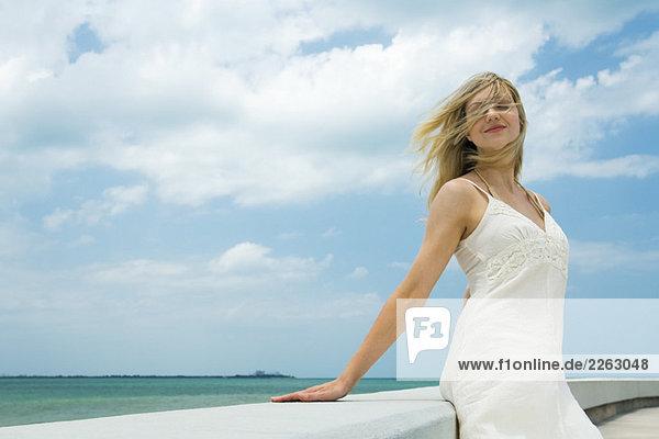 Junge Frau gelehnt gegen Ledge mit Augen geschlossen  Wind weht Haare über Gesicht  lächelnd