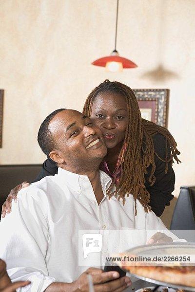 Mann und Frau im Restaurant  Mann hält Pizza