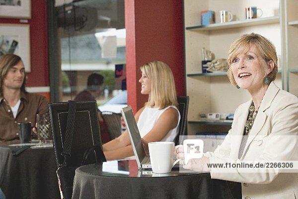 Frau mittleren Alters am Laptop in einem Café