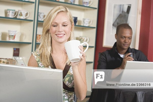 Blond woman in front of laptop in café  man in background