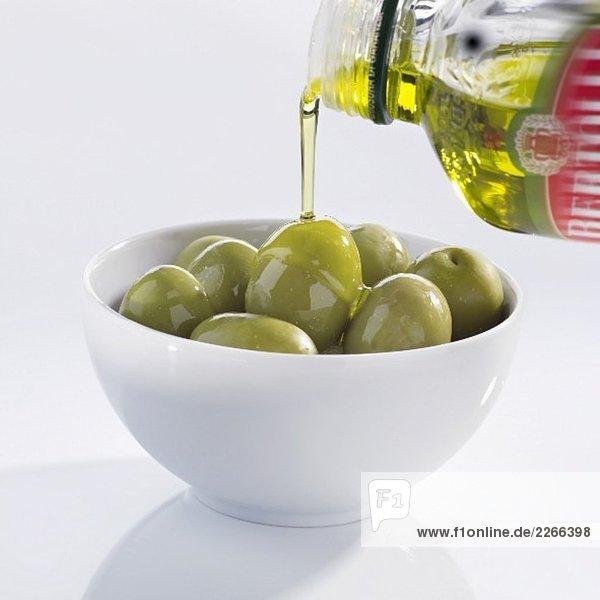 Olivenöl über Oliven giessen