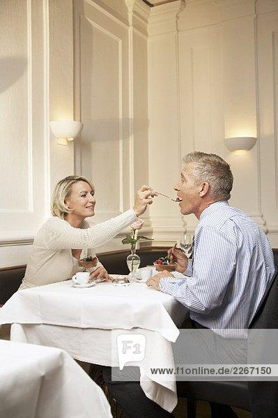 Paar mittleren Alters geniesst Dessert in einem Restaurant