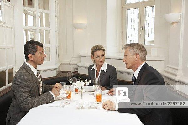 Drei Personen bei einem Geschäftsessen