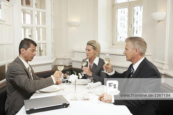 Drei Geschäftsleute bei gemeinsamen Essen