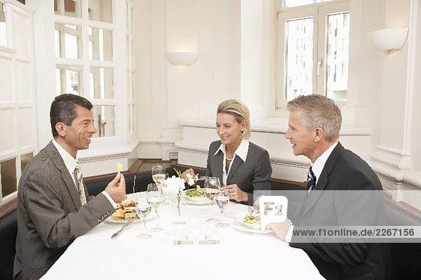 Frau und zwei Männer bei einem Geschäftsessen
